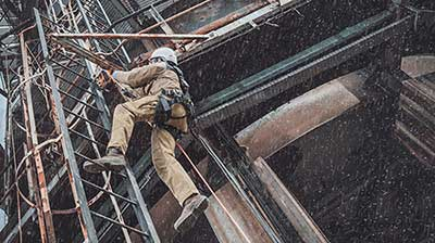 homme travaillant en hauteur sur échelle avec harnais de sécurité